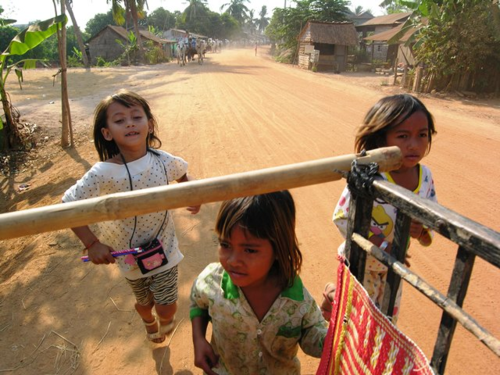 Children in the Cambodian village of Kampong Tralach run with ox carts hauling passengers from Avalon Angkor (Photo by David G. Molyneaux, TheTravelMavens.com)