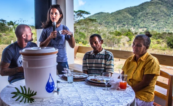 Tara Russell, standing, and Doc Hendley, left, of Wine to Water, introduce a new water filter to a family in the Dominican Republic (Photo by LenKaufman.com)