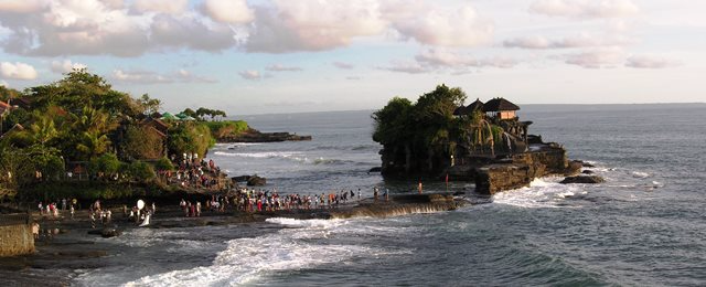 Every day at sunset in Bali, Indonesia, hundreds of Hindu followers and curious travelers gather at Tanah Lot temple, which stands on solid sea rock (Photo by David G. Molyneaux, TheTravelMavens.com)