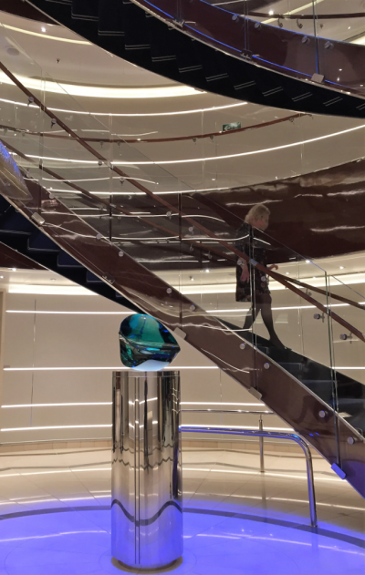 "Atrium stairway on Seabourn Ovation, designed by Adam Tihany: ""No matter what you wear when you walk down the stairway, you straighten up, make your grand entrance, because you look and feel great."" The art at the base is ""Warrior The Second,"" created by Luciano Vistosi from polished and hammered lagoon green crystal. (photo by David G. Molyneaux TheTravelMavens.com)"